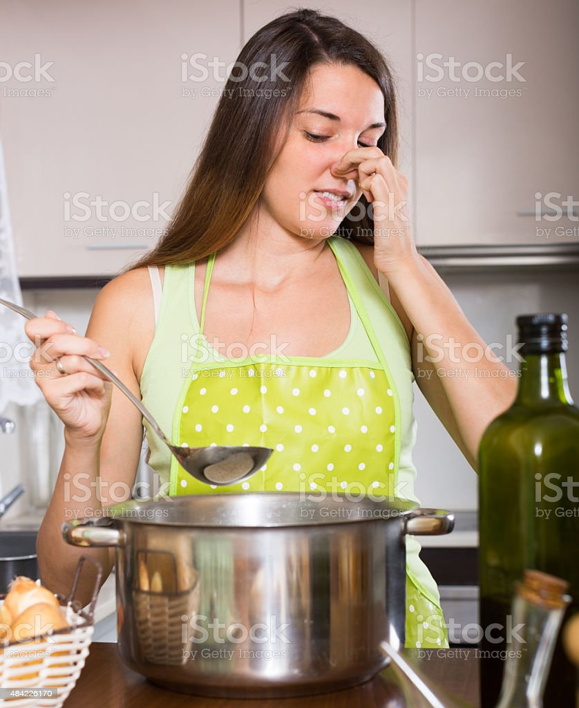 Housewife with bad smelling pan stock photo