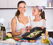 housewife with girl cooking pizza