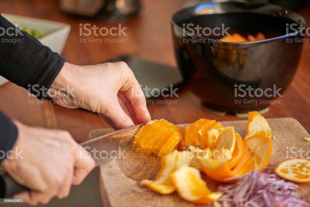 Housewife working in the kitchen cutting oranges stock photo