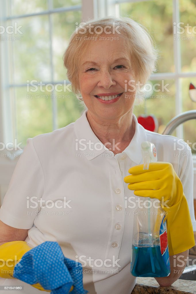 Housework:  a senior woman getting ready to clean her kitchen stock photo
