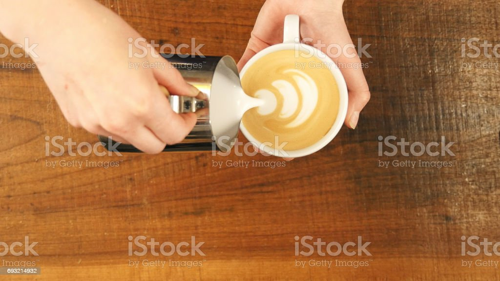 How to make latte art by barista focus in milk and coffee stock photo