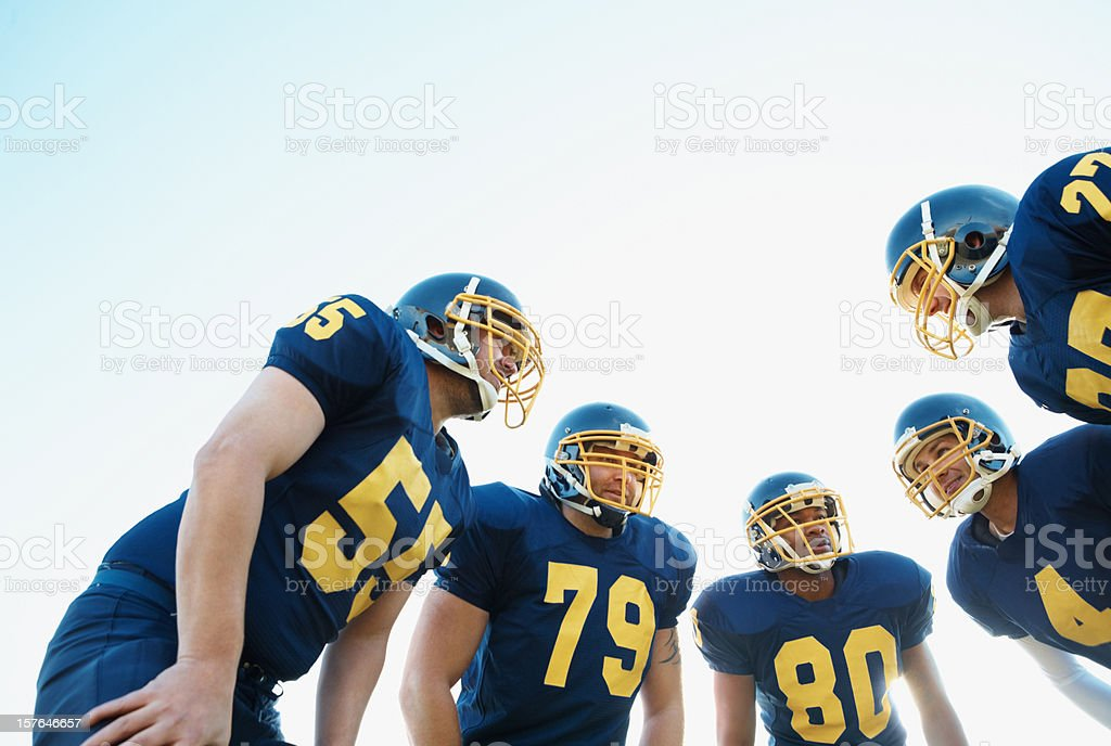 Huddle of Pro American football team against clear sky stock photo