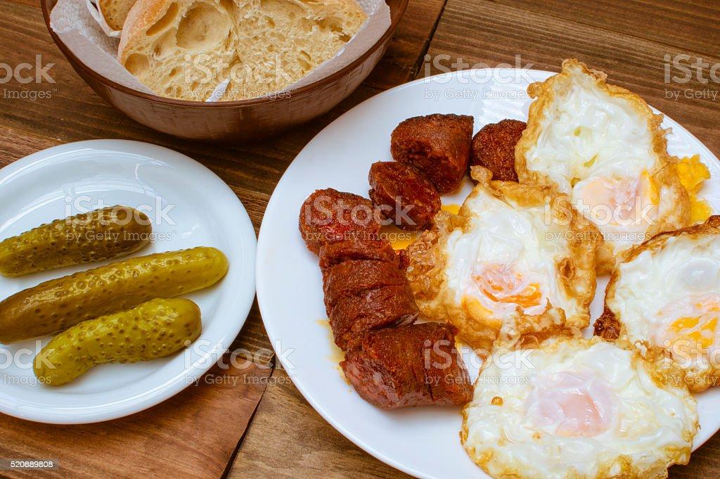 Huevos fritos, au chorizo Frito, pepinillos photo libre de droits