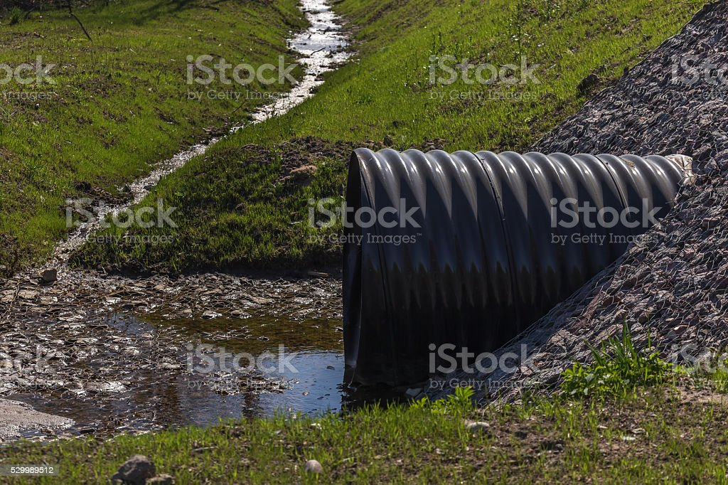huge black plastic sewer and small stream stock photo