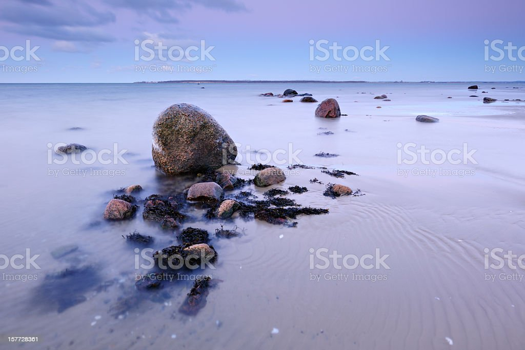 Huge Boulders on Rippled Sand Beach at Sunset royalty-free stock photo