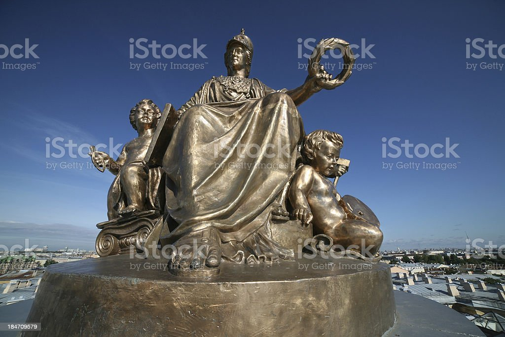 Huge bronze statue surrounded by geniuses of Arts stock photo