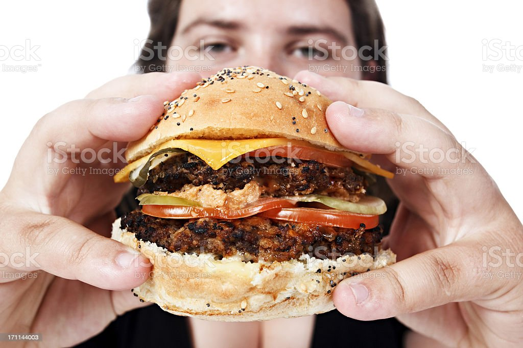 Huge cheeseburger dwarfs the plump young eater stock photo
