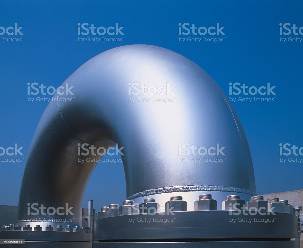 Huge curved metallic pipe in a gas distribution plant stock photo