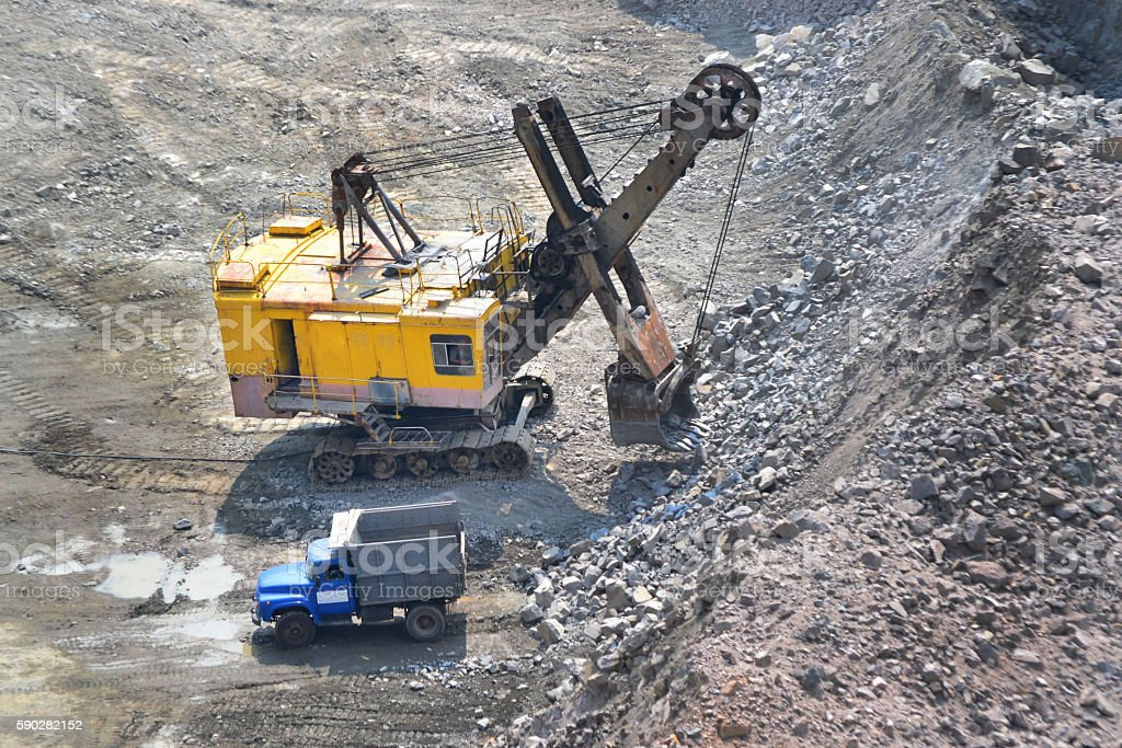 huge excavator and a truck on granite quarry stock photo