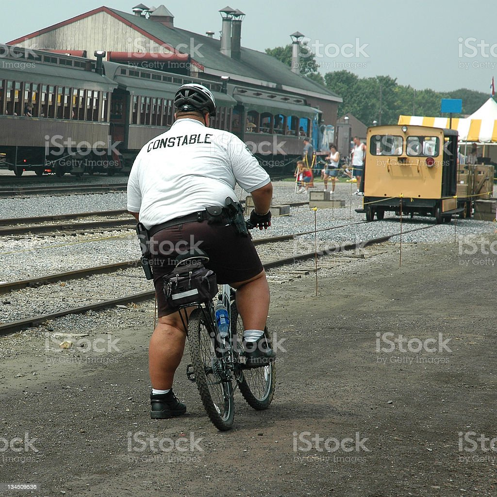 Huge Fat Obese Police Officer On Bike Near Train Tracks royalty-free stock photo