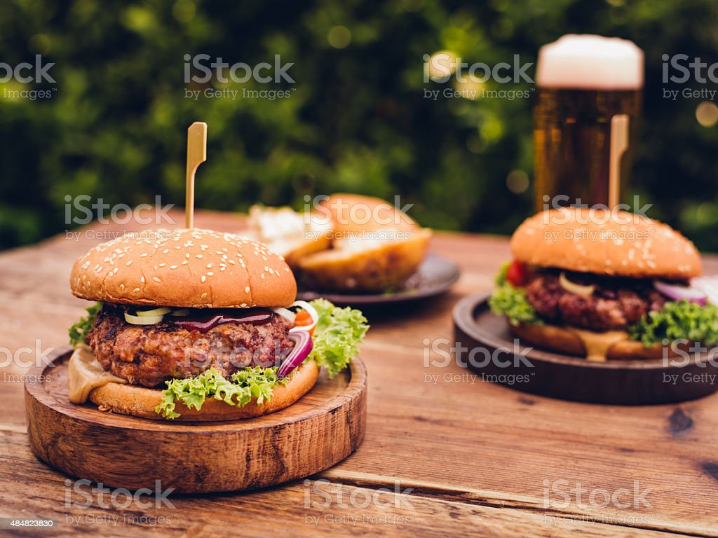 Huge gourmet cheese burgers on a rustic wooden table outdoors stock photo