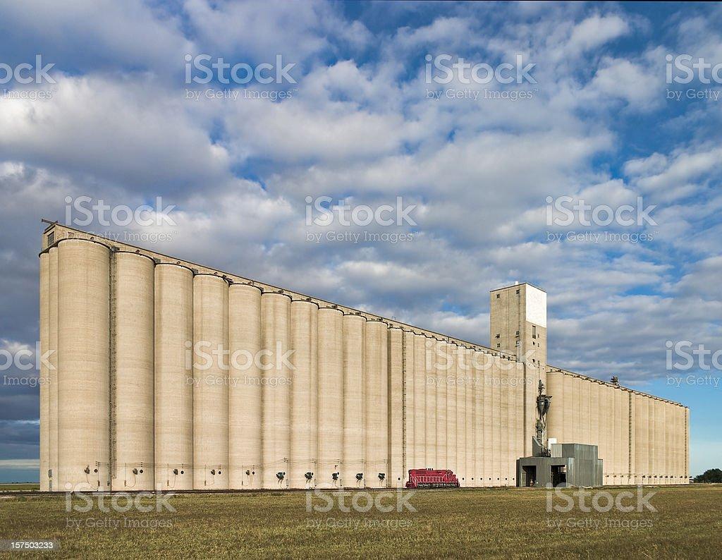 huge grain elevator dwarfs red train locomotive stock photo