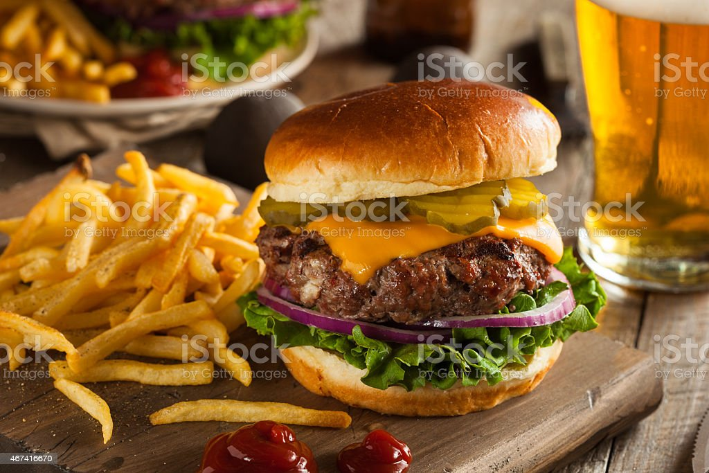 Huge grass fed bison hamburger with chips & beer stock photo