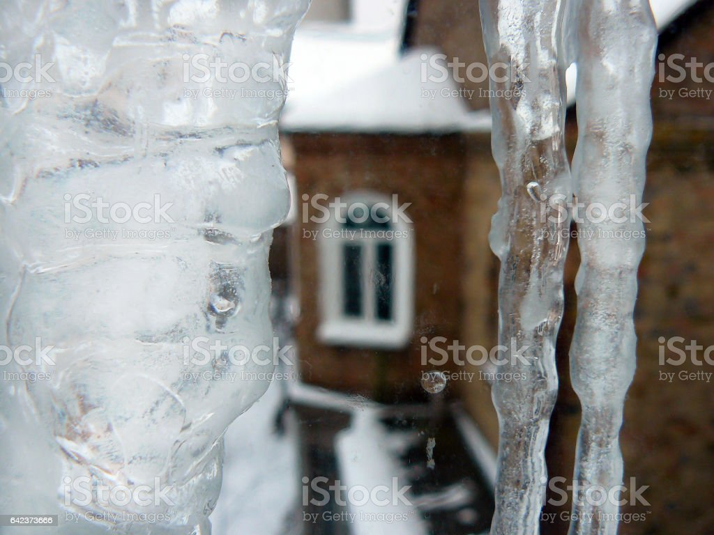 Huge Icicles in front of a Family House Window stock photo