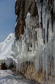 Huge icicles on rocks. Beautiful winter landscape in Lake Baikal.