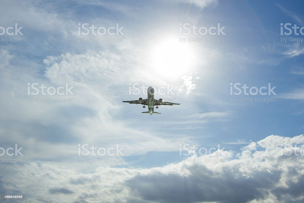 Huge Jet Plane landing flying blue sky white clouds background stock photo