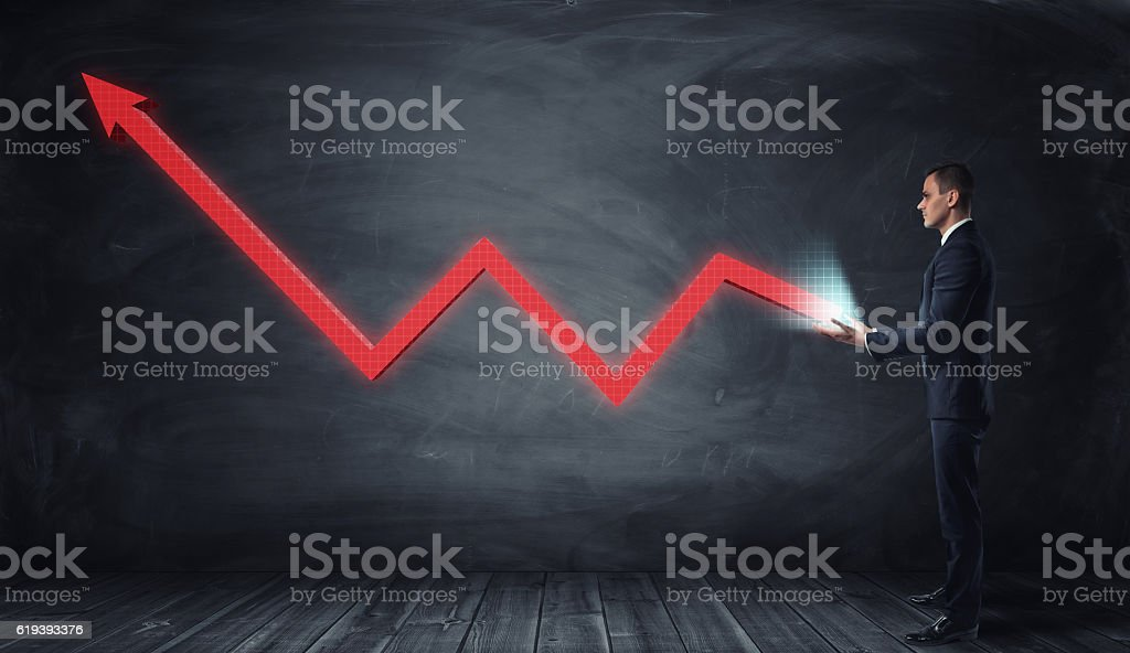 Huge red line graph with an upturned arrow growing from stock photo