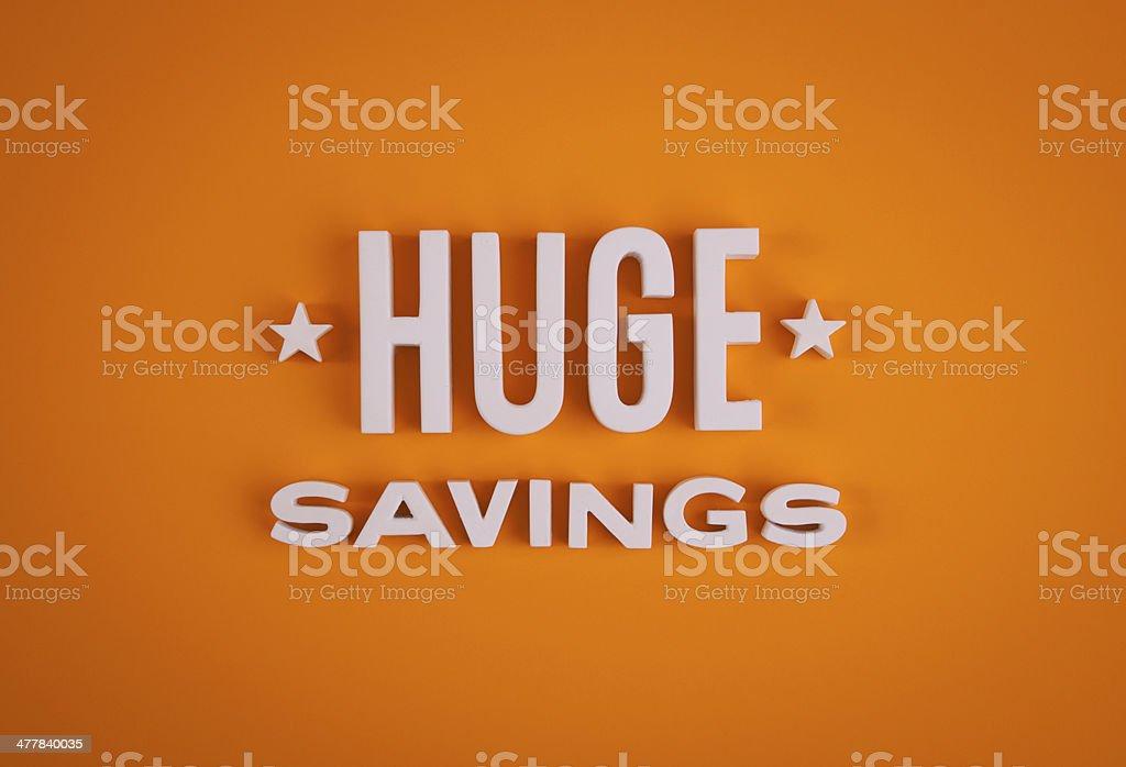 Huge Savings sign lettering stock photo