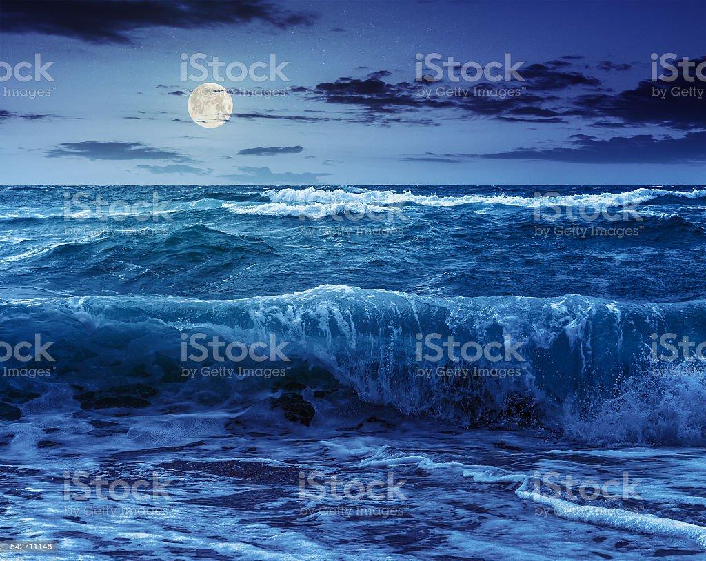 huge sea waves running on sandy beach at night stock photo