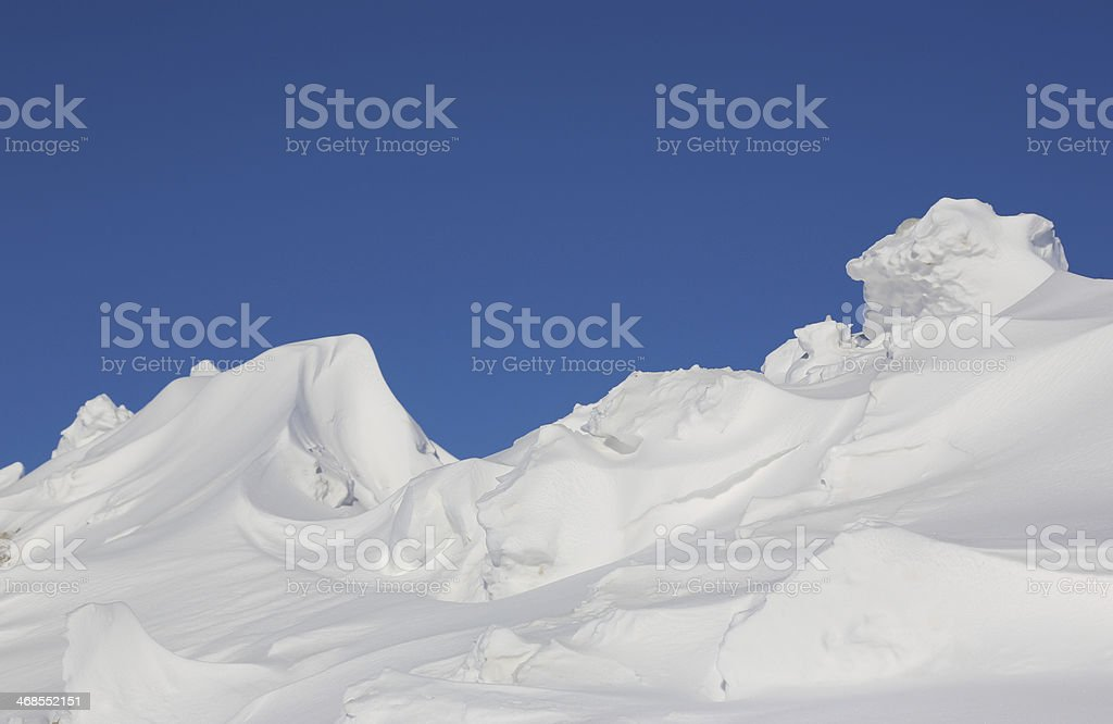 Huge snowdrifts in winter against blue sky royalty-free stock photo