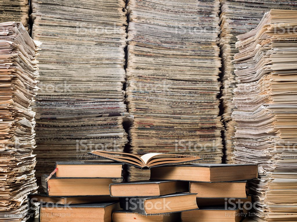Huge stack of hardcover books and newspapers in library stock photo