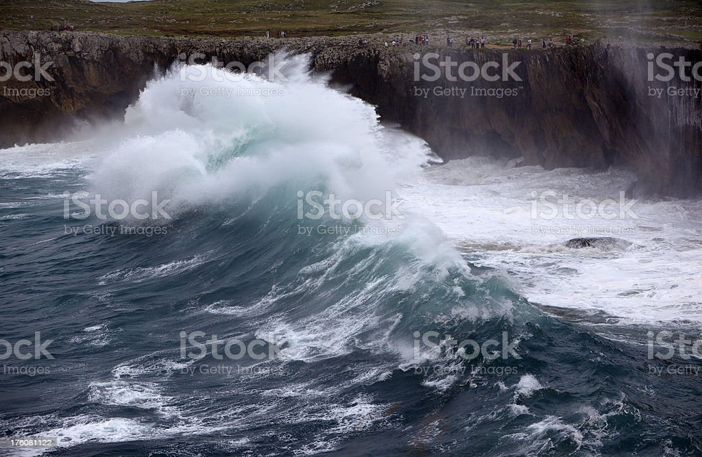 Huge tidal wave about to strike coast cliff with people stock photo