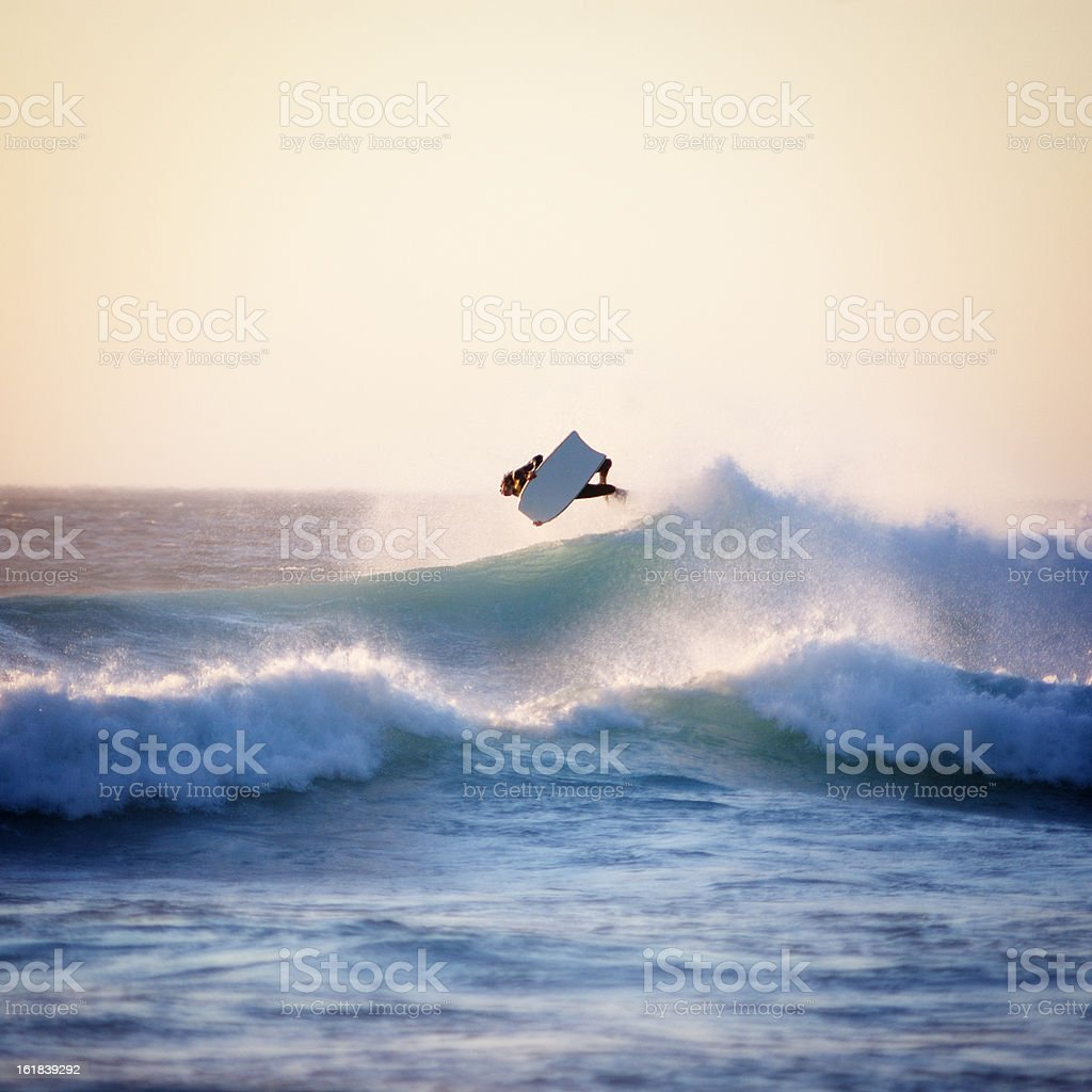A huge wave with a bodyboarder flying on top stock photo