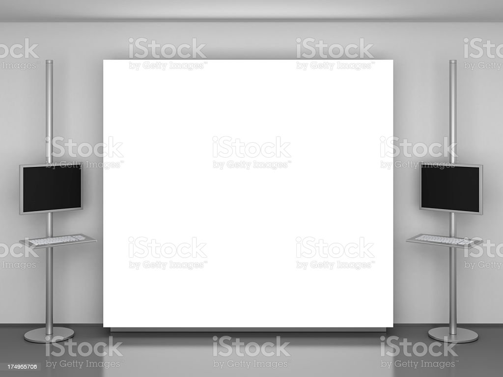 A huge white screen beside two monitor screens with keyboard royalty-free stock photo