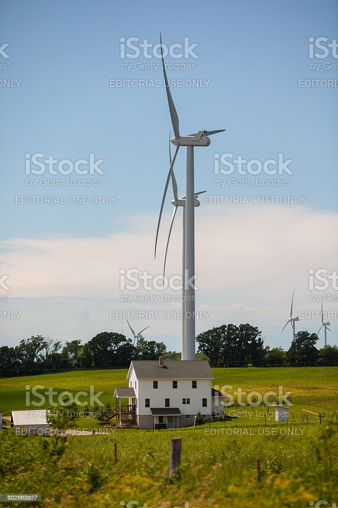 Huge windmill dwarfing a farmhouse. stock photo