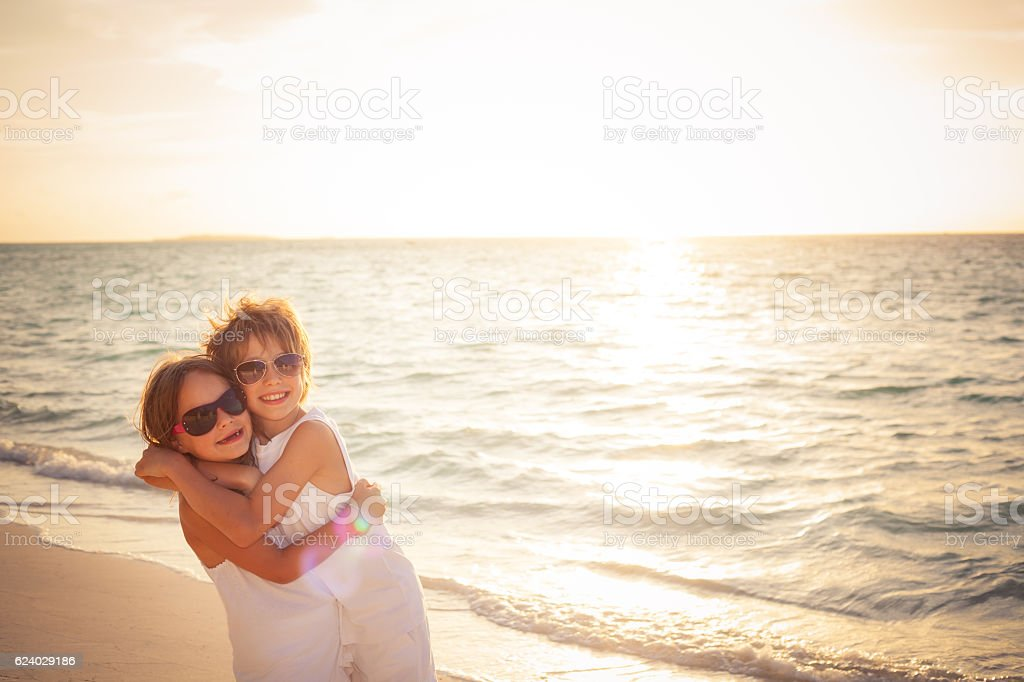 hugging brother sister sunet beach stock photo
