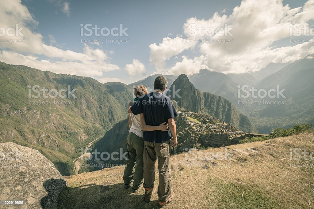 Hugging couple looking at Machu Picchu, Peru, toned image stock photo