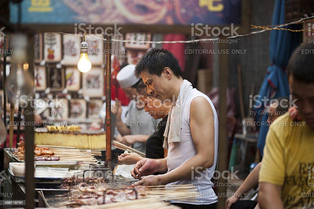 Hui man grilling skewers at Muslim Street in Xian royalty-free stock photo
