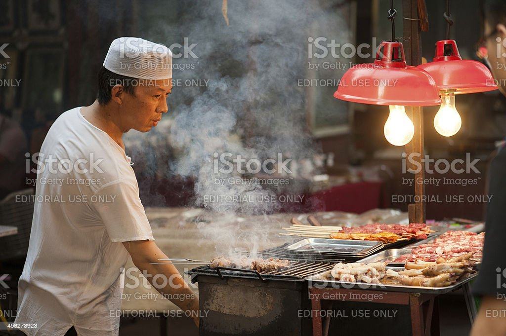 Hui man grills mutton skewers at lively Muslim Street royalty-free stock photo