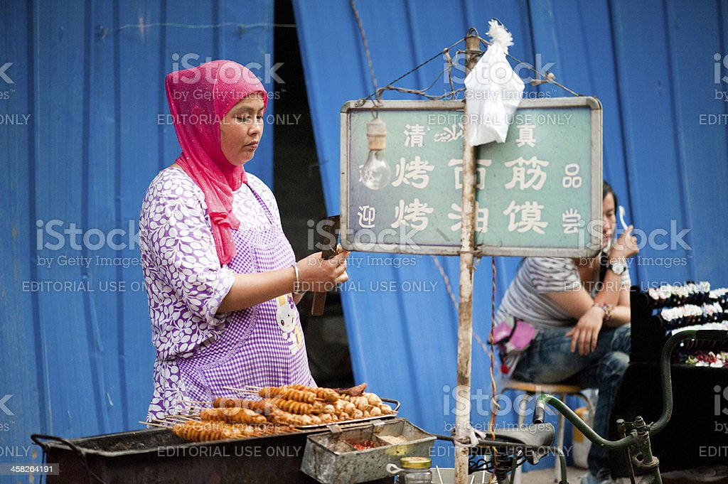 Hui woman preparing mutton skewers at Muslim street royalty-free stock photo