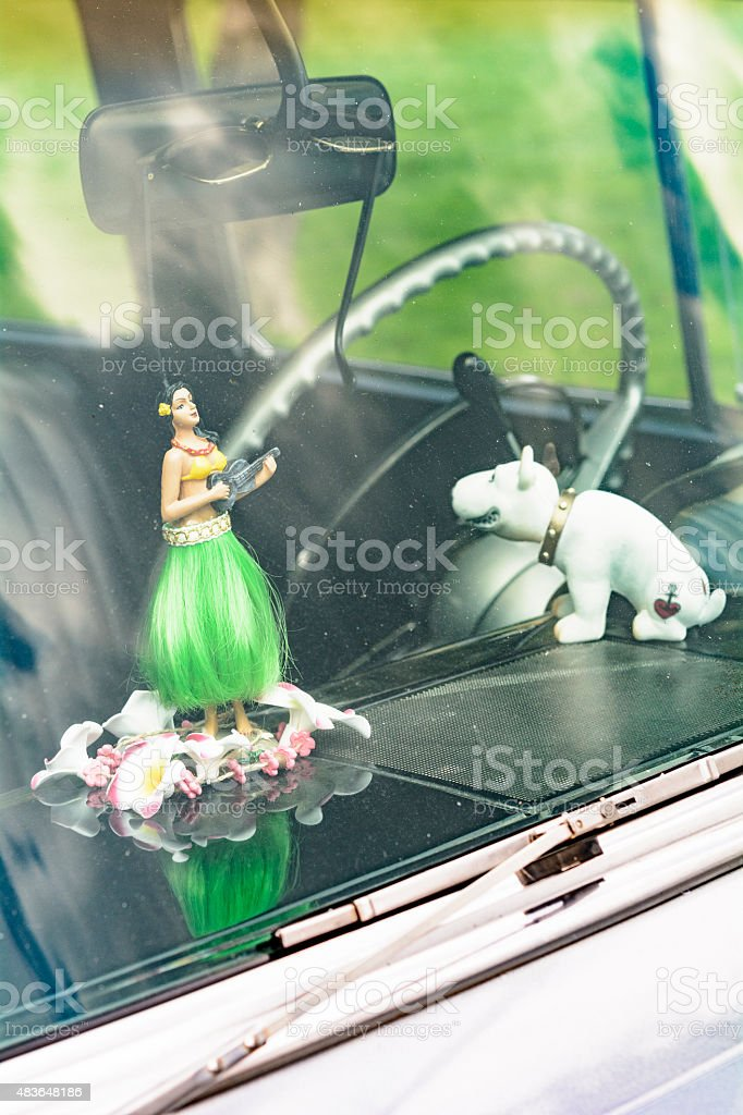 Hula girl doll and bobble head dog on the dashboard stock photo