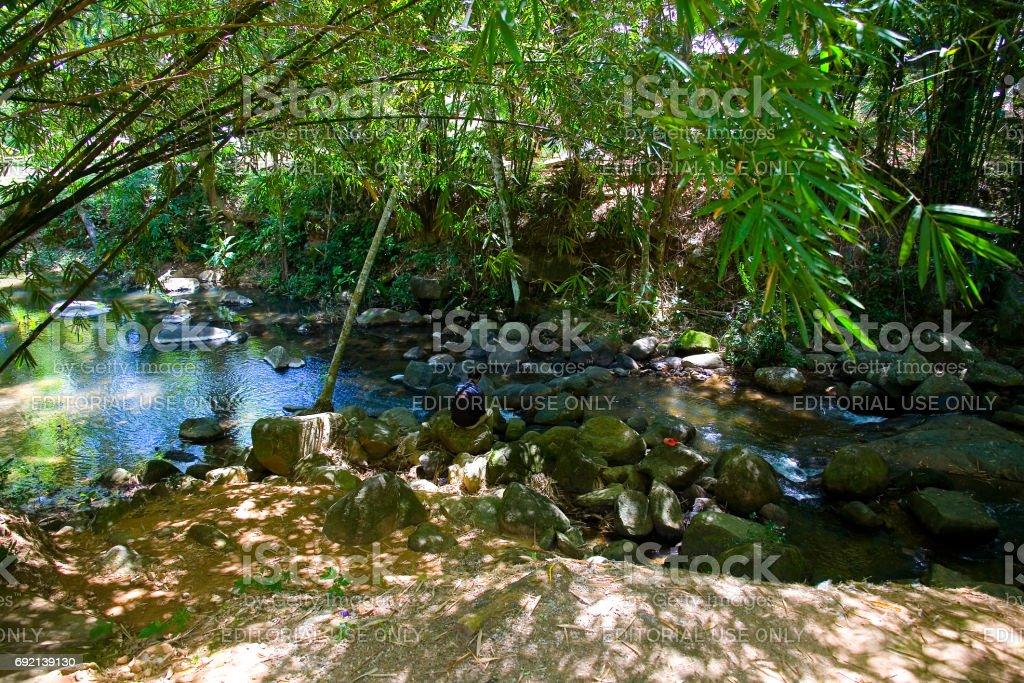 Human and nature. A man sits on rocks in a picturesque place by a mountain river. stock photo