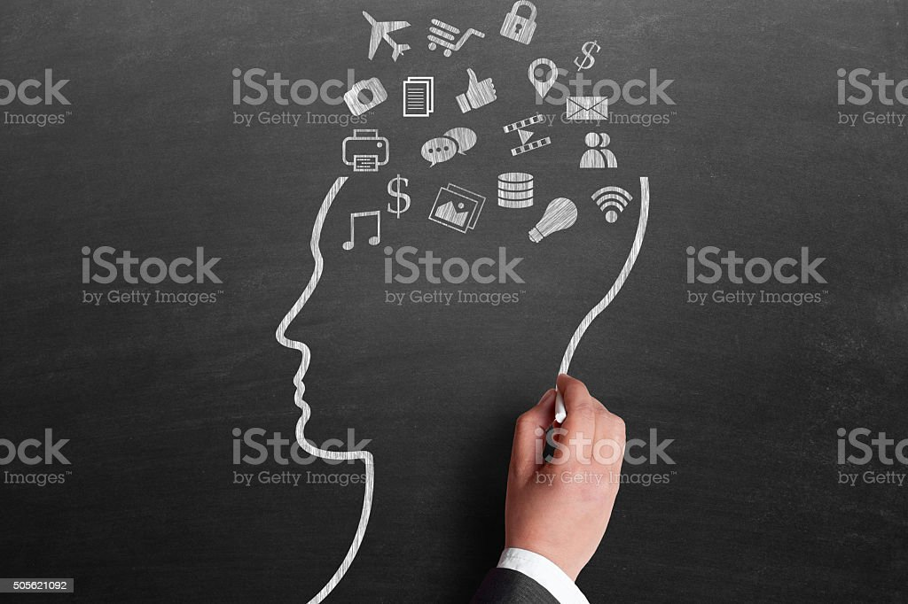 Human brain with variety of icons drawn on blackboard stock photo