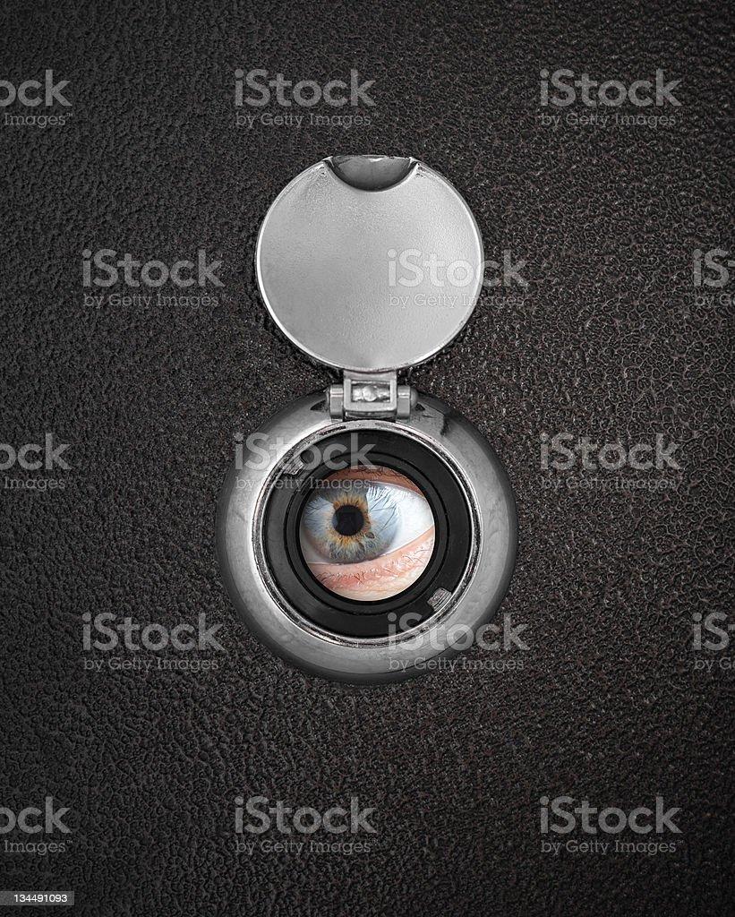 Human eye in peep hole closeup stock photo