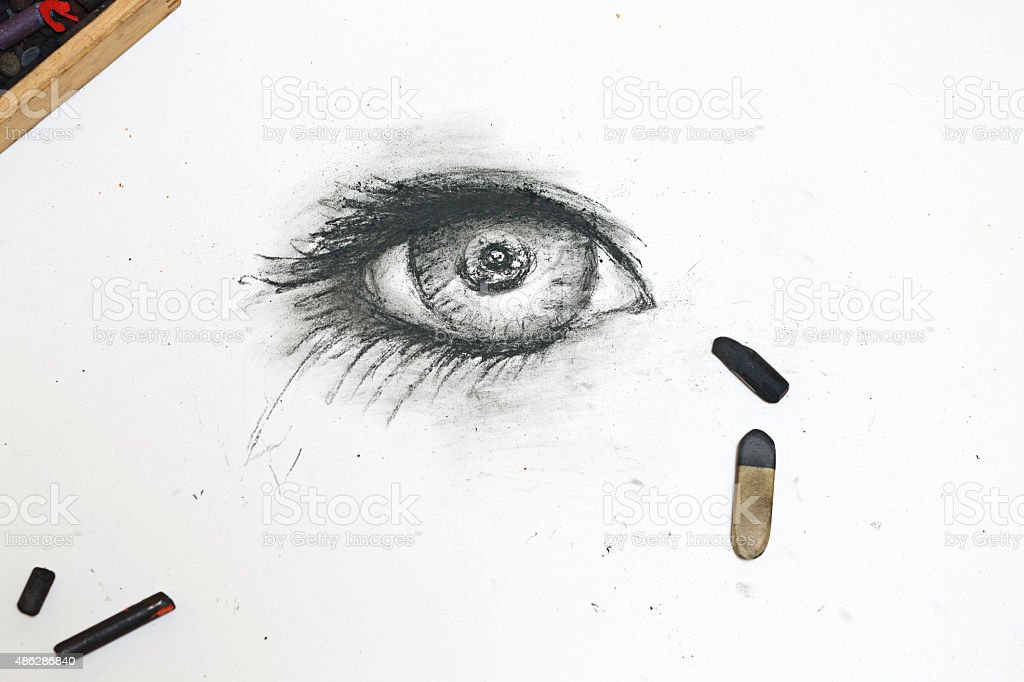 Human eye is drawn in charcoal on paper. stock photo