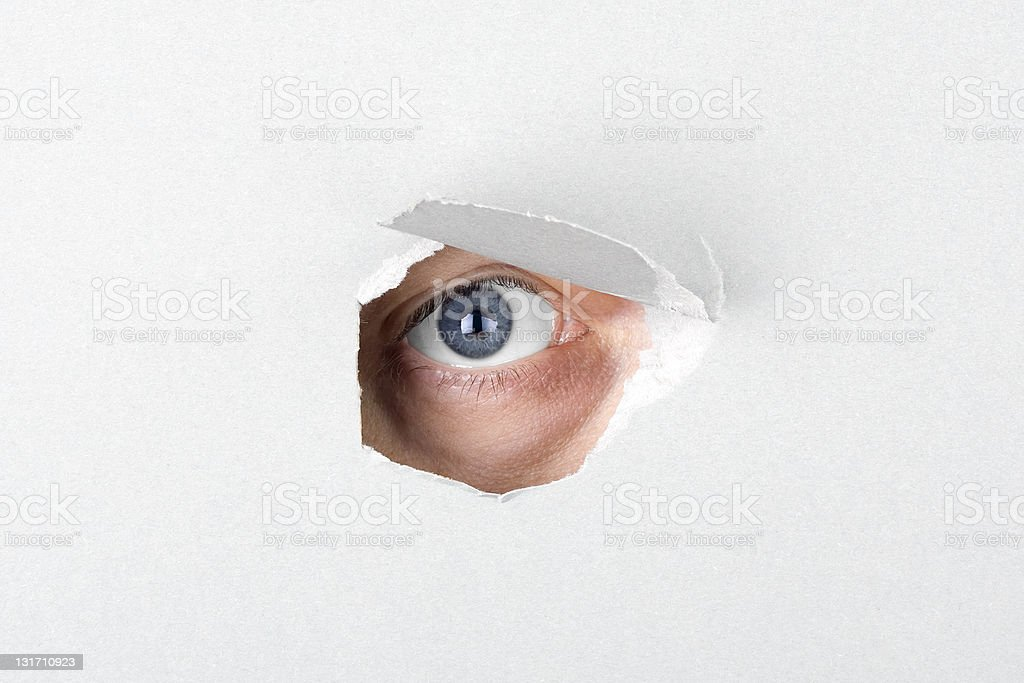 Human eye looking through a paper hole royalty-free stock photo