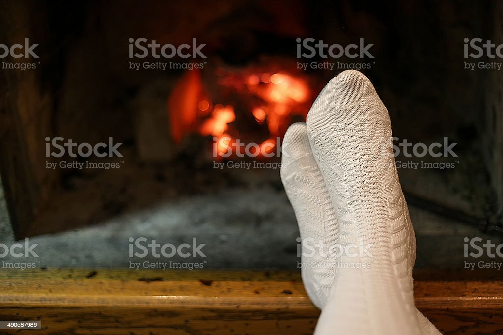 Human feet in wool socks warming by fireplace stock photo
