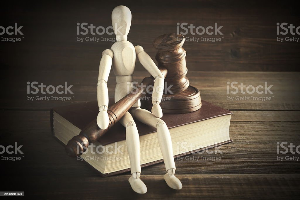 Human Figurine With Judges  Or Auctioneer  Gavel Sit On  Book stock photo