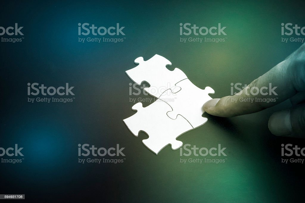 human finger pointing to jigsaw puzzle pieces stock photo