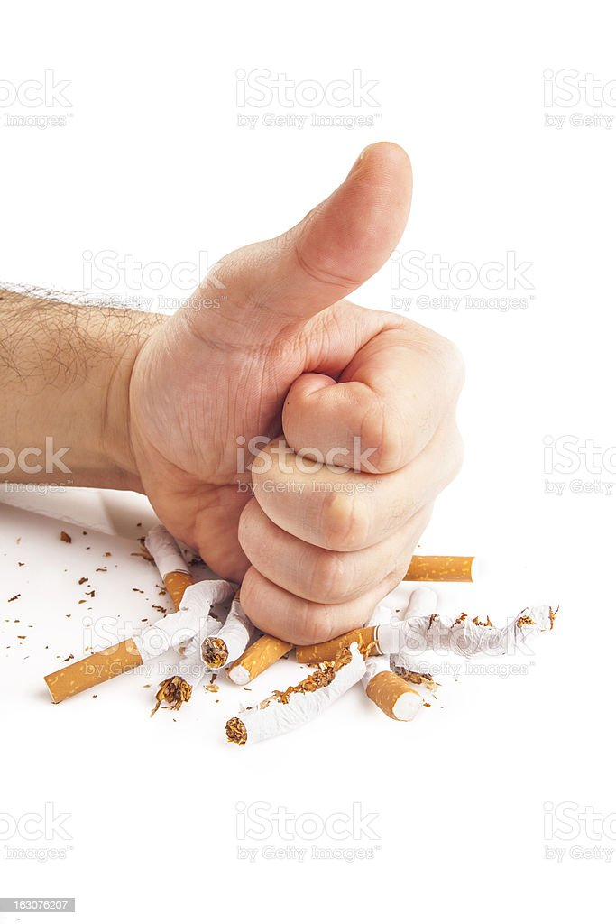 Human fist breaking cigarettes on white background royalty-free stock photo