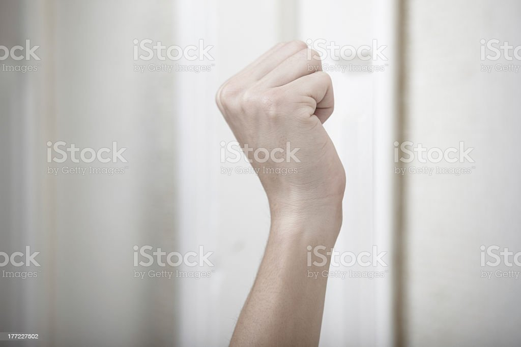 Human fist hovering in front of door, getting ready to knock stock photo