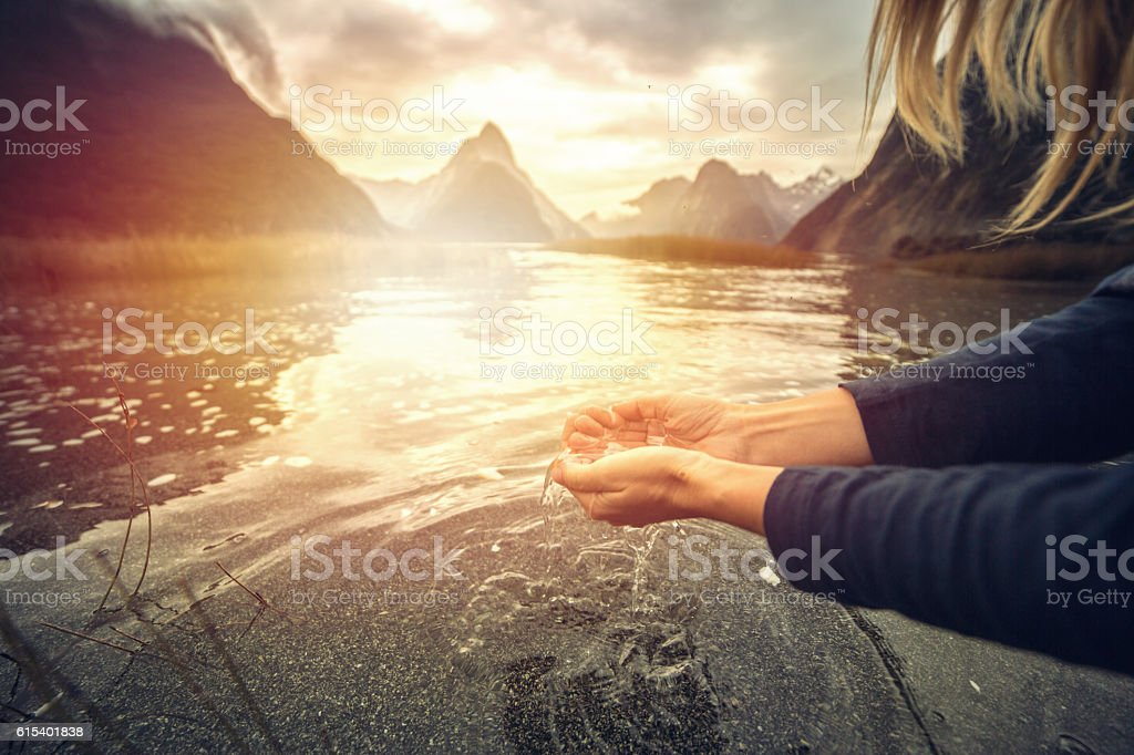 Human hand cupped to catch fresh water from lake, NZ stock photo