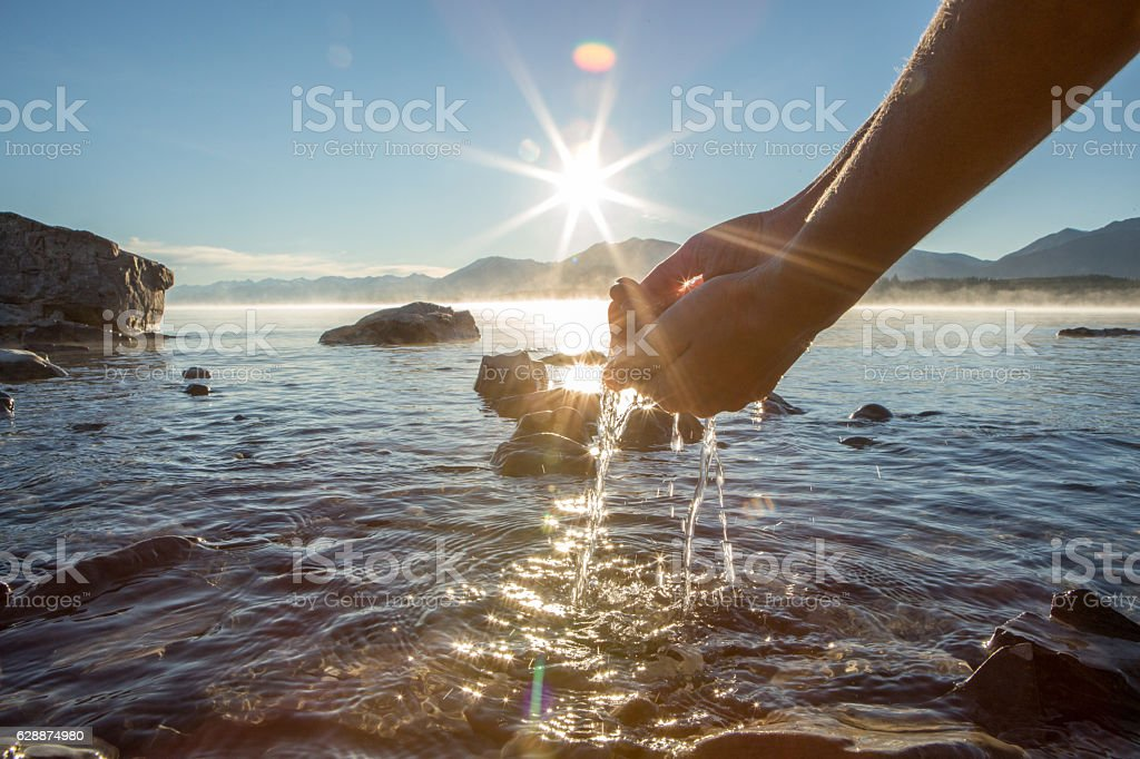 Human hand cupped to catch fresh water from lake stock photo