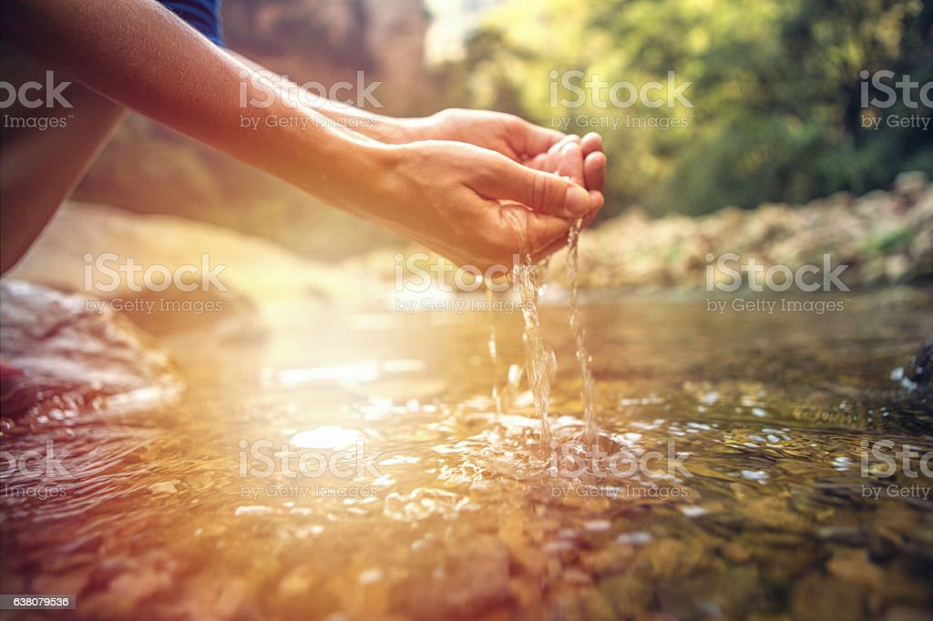 Human hand cupped to catch fresh water from river stock photo