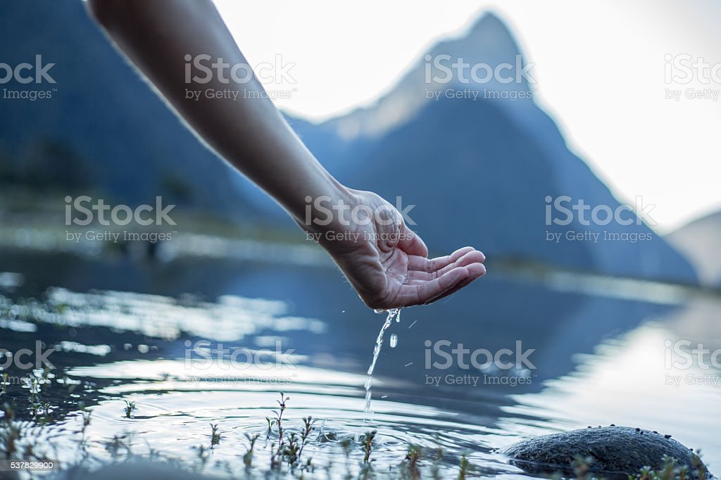 Human hand cupped to catch fresh water from the lake stock photo