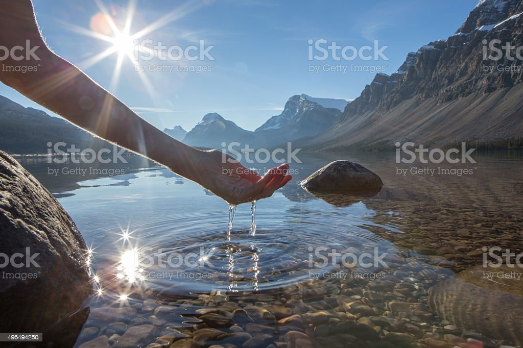 Human hand cupped to catch the fresh water from lake stock photo